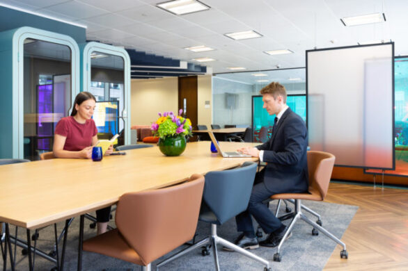 man and woman sitting at a desk in a meeting room