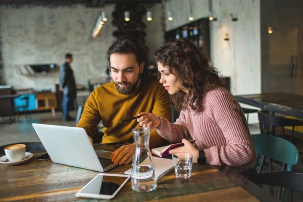 couple looking at laptop in coffee shop